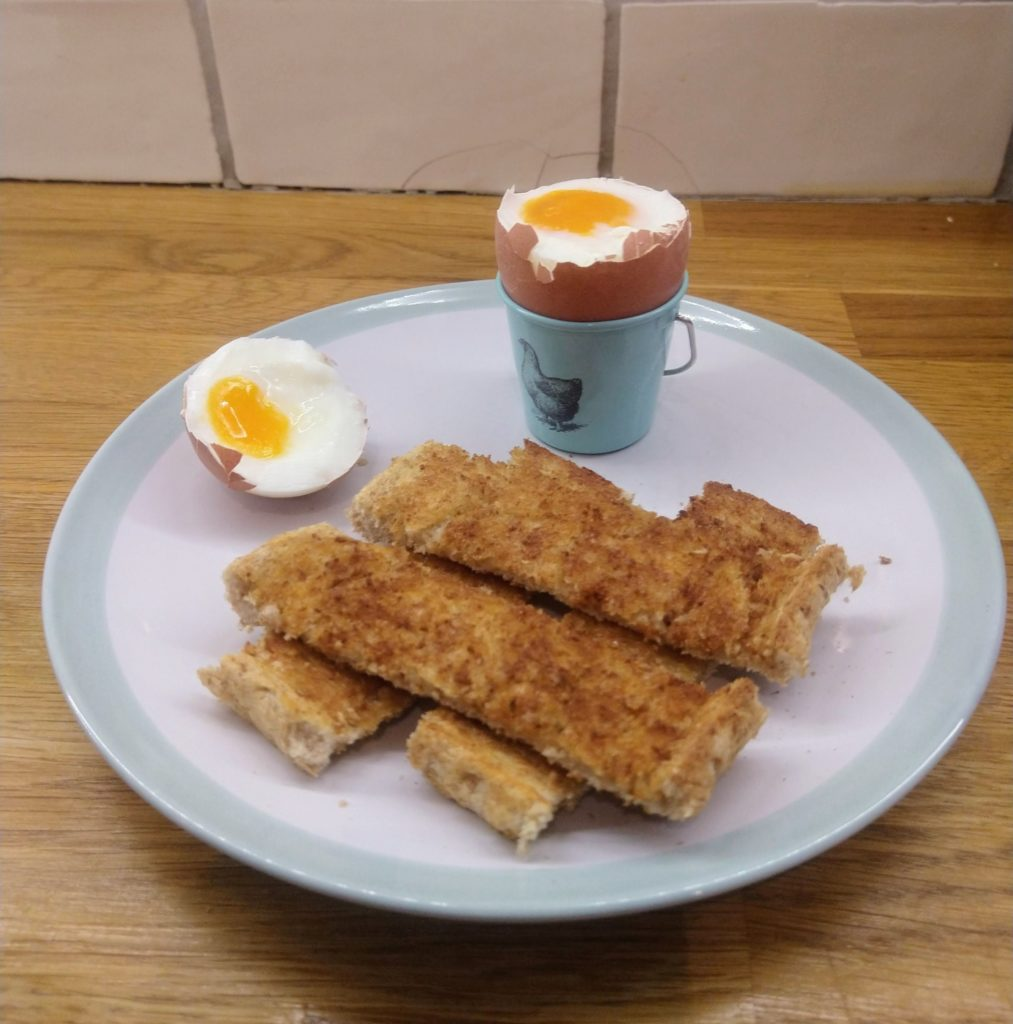 A plate witha soft boiled egg in an egg cup boiled in an instant pot with a side of buttered toast